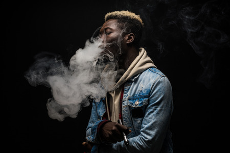 African Man vaping an electronic cigarette isolated on black