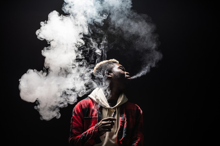 Young thinking serious concentrated african man standing and smoking electronic cigarette isolated on gray background Imagens