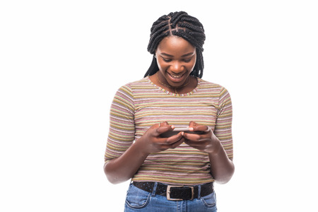 Cheerful young African American female holds cell phone in hands, glad to recieve message from lover, sends photos and video, smiles gladfully. People and lifestyle concept.