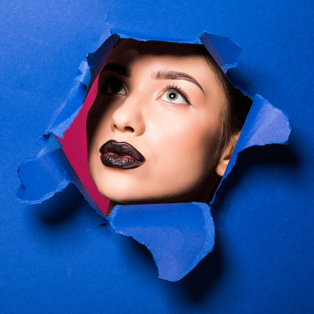 The face of young beautiful girl with a bright make-up and puffy dark lips peers into a hole in blue paper.