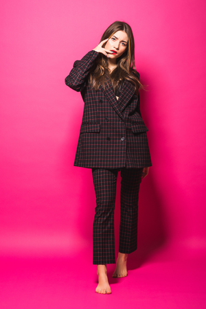 Full length photo of fashion woman in dress looking aside and touching trendy sunglasses over pink background Stock fotó