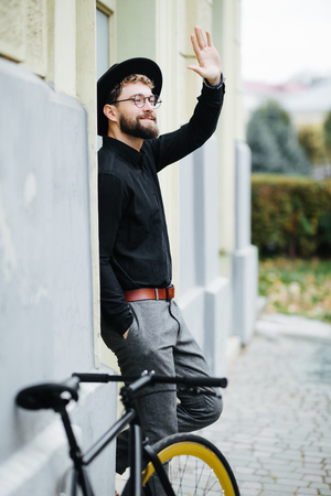 Happy young hipster man with fixed gear bike waving hand on city street