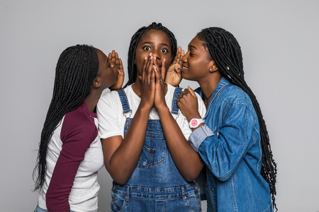 Three african girl friends sharing gossip isolated on white background