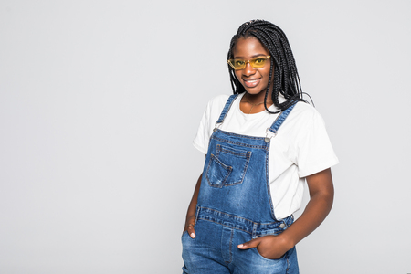 Portrait young beautiful attractive African American woman with trendy clothes and sunglass smiling on white studio background