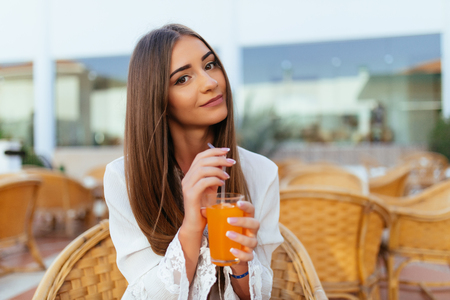 Portrait of happy gorgeous woman drinks fresh orange juice and cappuccino enjoys leisure time at outdoor terrace cafe, has rest in resort city during summer vacations. Leisure and people concept