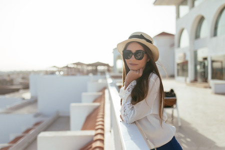 Beautiful European girl in a straw hat and sunglasses is relaxing on resort balcony against seaside. Standard-Bild