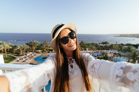 Young woman girl taking a selfie is looking on a sunny day in the summer to the sea from a balcony. Stock Photo