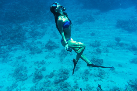 Young woman snorkeling with camera take photo over coral reef in blue transparent sea