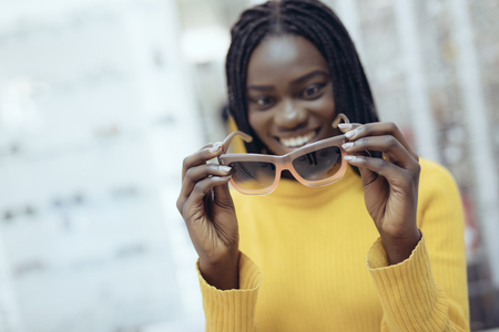 Young african woman in casual clothes try different sunglasses in optical store