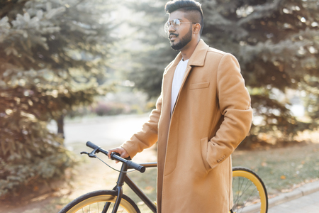 Young bearded indian man drinking coffee while standing on his bicycle outdoors