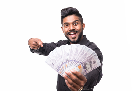 Happy joyful handsome young indian businessman holding dollars and winking with open mouth isolated on white background