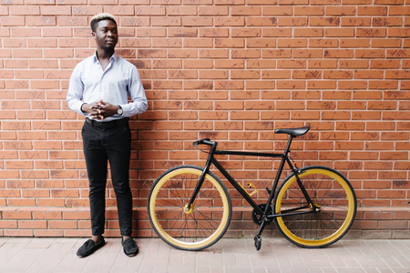 Stylish african man standing with his bicycle against brick wall