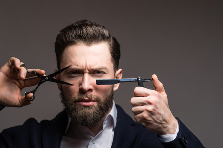 Barbershop advertising concept. Businessman with serious face isolated on black background. Man with long beard holds steel scissors. Macho in formal suit cuts beard and moustache. Reklamní fotografie