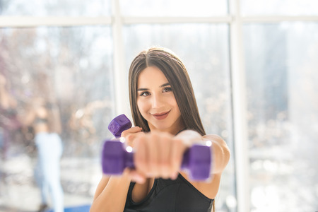 Muscular young woman with beautiful body doing exercises with dumbbell. Foto de archivo