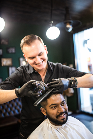 Hairdresser cuts hair, with scissors and black comb, on crown of handsome satisfied client on barber shop 版權商用圖片