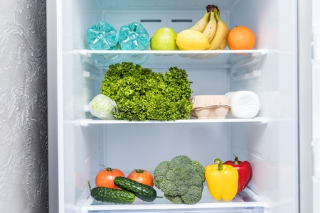 Open fridge full of fresh fruits and vegetables, healthy food background, organic nutrition, health care, dieting concept Archivio Fotografico