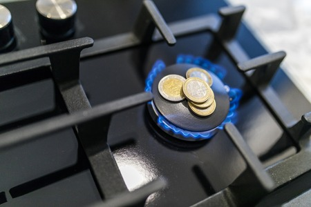 Cost of gas, concept crisis. Gas stove with coins in flame. The cost of methane. Gas coins more expensive