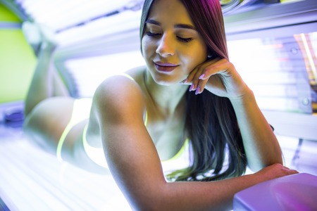 young girl in a bathing suit sunbathing in a horizontal solarium under the ultraviolet rays