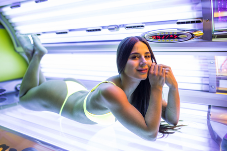 Young beautiful latin lady lying on a tanning bed at health spa 스톡 콘텐츠