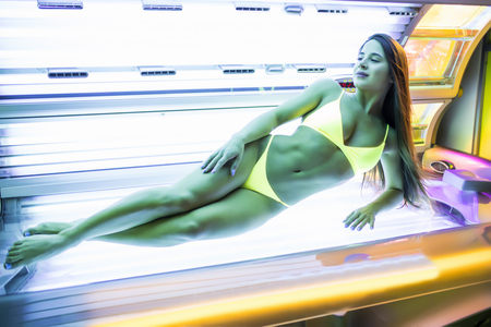 young woman at laying on solarium bed and get brown skin tone ready for summer Stock Photo