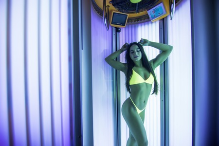 pretty woman or cute girl with sexy naked healthy body standing in solarium spa salon Standard-Bild