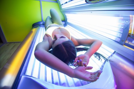 Young attractive brunette girl is laying in the working solarium