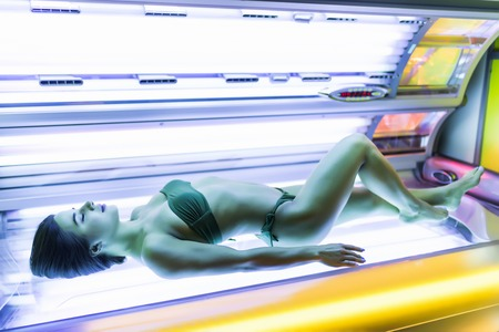 shapely young girl sunbathing in a solarium, wants a beautiful tanned skin Stock Photo