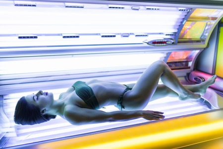 youn girl in a bathing suit sunbathing in a horizontal solarium under the ultraviolet rays