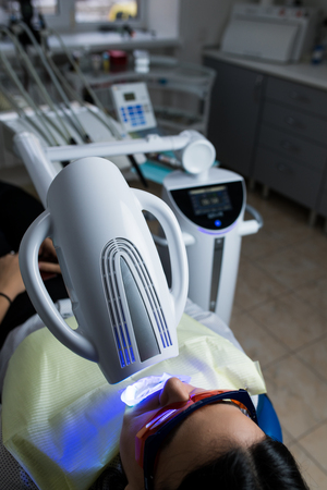 Laser bleaching teeth at dantist room. Teeth whitening for woman. Bleaching of the teeth at dentist clinic Stock Photo