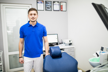 Portrait of a dentist. Young man at his workplace in the dental clinic Stock Photo