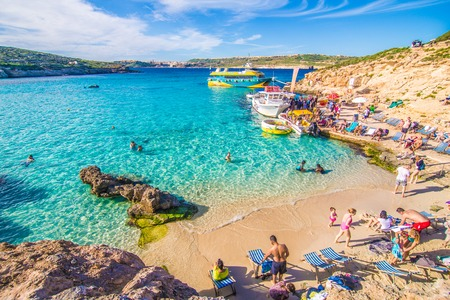 Comino, Malta - November, 2018: Tourists crowd at Blue Lagoon to enjoy the clear turquoise water on a sunny summer day with clear blue sky and boats