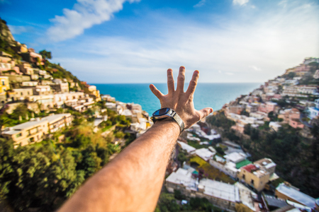 Man hand in front of Positano shore view