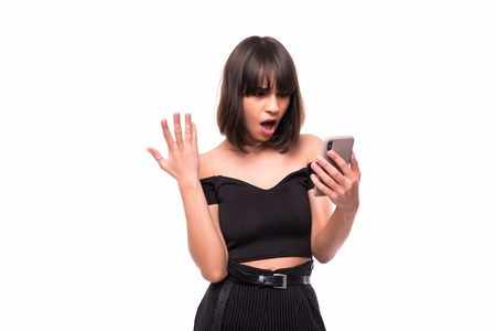 Annoyed angry young woman mad about spam message stuck phone looking at smartphone isolated on blank studio background, furious teen girl having problem with cellphone irritated by broken mobile