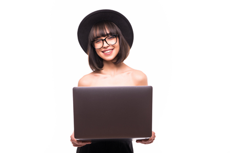 Portrait of young woman in summer clothes, black floppy hat using laptop isolated on white background.