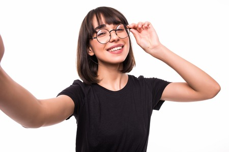 Smiling young woman casualy dressed standing isolated over white background, taking a selfie with outsretched hands Stockfoto