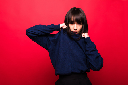 Cheerful beautiful woman in sweater over red background Archivio Fotografico