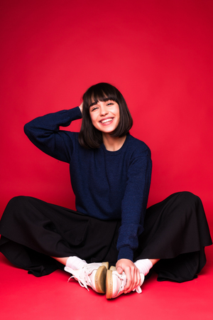 Laughing brunette sitting on the floor, pointing away and winks at the camera over red background 版權商用圖片