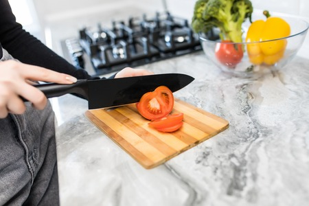 Closeup of young woman cutting tomato for salad in kitchen