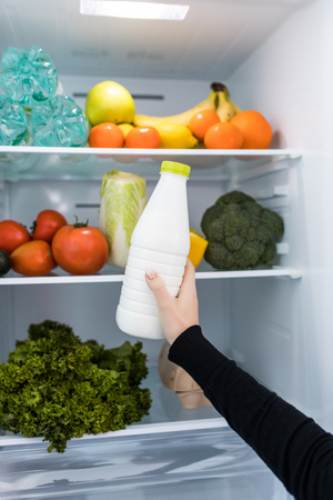 Woman standing in front of fridge and taking milk.