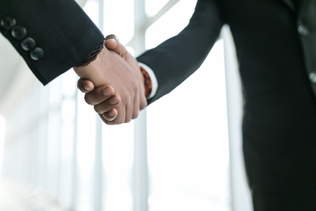 Two confident business man shaking hands during a meeting in the office Imagens
