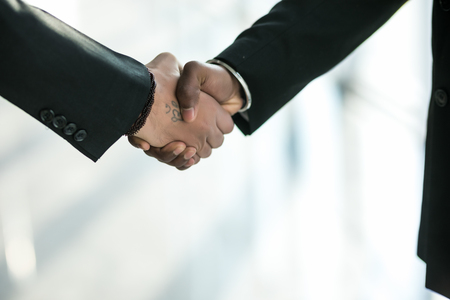 Business shaking hands in modern building with copy space