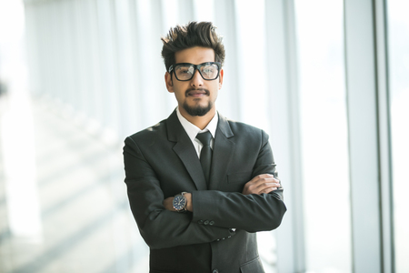 Portrait of young businessman with glasses in suit with crossed hands near window in modern office. Foto de archivo - 120721553