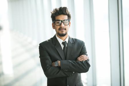 Retrato de joven empresario con gafas en traje con las manos cruzadas junto a la ventana en la oficina moderna.