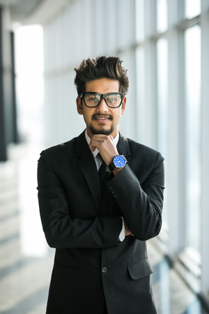 Portrait of young businessman with glasses in suit with crossed hands near window in modern office.