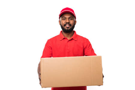 Side view of young delivery man with box. isolated gray background Stock Photo