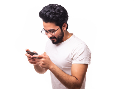Excited bearded man playing on smartphone isolated over white background Stock Photo