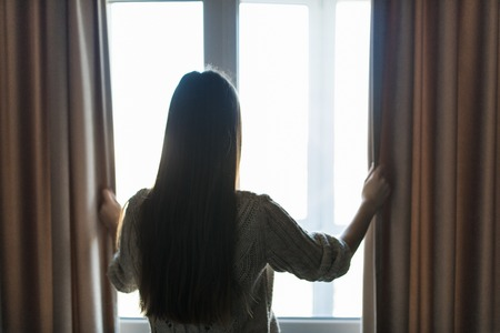 Rear view - young fit woman in home clothes opens curtains of bedroom window. Young girl is ready for new plans and new challenges. Imagens