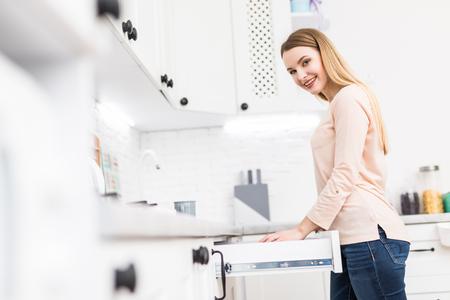 Ritratto di donna aperta a mano cassetto della cucina dalla moderna maniglia della porta