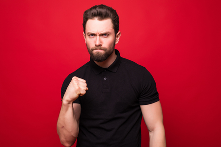 Portrait Of Angry Young Man Clenching His Fist On Red Background Stock Photo