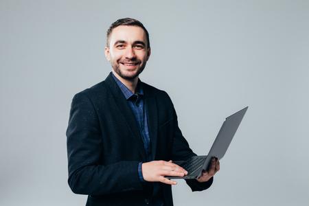 Seitenansicht eines attraktiven Geschäftsmannes im klassischen Anzug mit Laptop, der vor grauem Hintergrund steht Standard-Bild